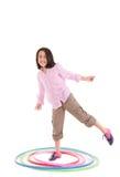 Ung flicka som spelar med hulabeslaget som över isoleras Arkivfoto