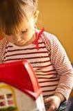 Ung flicka som spelar med leksaken Arkivfoton