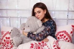 Ung flicka som spelar med nallebjörnen i säng Fotografering för Bildbyråer