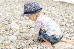 Ung flicka som spelar med stenar på stranden Royaltyfria Bilder