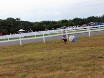 Ung flicka som spelar med strandbollen fotografering för bildbyråer