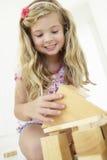 Ung flicka som spelar med träbyggnadskvarter i sovrum Arkivfoto