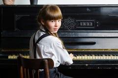 Ung flicka som spelar pianot inomhus arkivbild