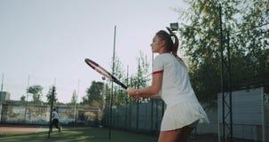 Ung flicka som spelar tennis på tennisbanan, bra solig dag, yrkesmässig spelare lager videofilmer