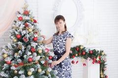 Ung flicka som står den near julgranen Royaltyfri Bild