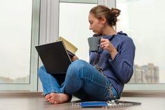 Ung flicka som studerar och dricker kaffe Royaltyfri Bild
