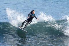 Ung flicka som surfar en våg i Kalifornien arkivbilder