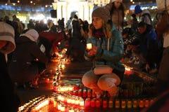 Ung flicka som tänder en stearinljus i Kyiv Arkivbild
