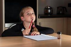 Ung flicka som tänker, medan göra läxa Royaltyfri Bild