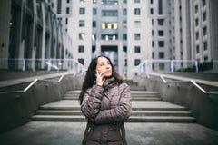 Ung flicka som talar på mobiltelefonen i borggårdaffärsmitt flicka med det långa iklädda vinteromslaget för mörkt hår i kallt väd fotografering för bildbyråer