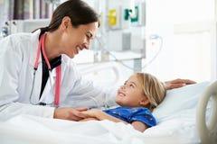 Ung flicka som talar till den kvinnliga enheten för doktor In Intensive Care Royaltyfri Foto
