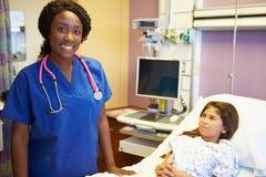 Ung flicka som talar till den kvinnliga sjuksköterskan In Hospital Room arkivfoton