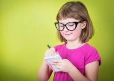 Ung flicka som tar anmärkningar arkivfoton