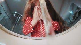 Ung flicka som tvättar hennes framsida i ett badrum och ser sig i spegeln stock video