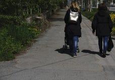 Ung flicka som två tillsammans går två lyckliga eleganta flickor som kör på våren, går, den tillbaka sikten, kamratskapbegrepp arkivbild