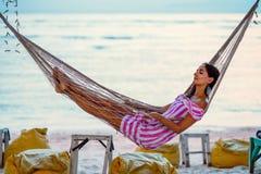 Ung flicka som tycker om aftonen som ligger i en hängmatta på kusten arkivbild