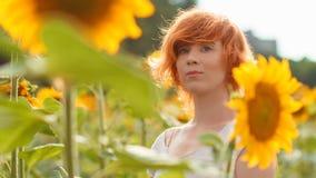Ung flicka som tycker om naturen på fältet av solrosor på solnedgången, royaltyfria bilder