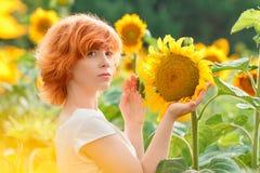 Ung flicka som tycker om naturen på fältet av solrosor på solnedgången, arkivfoto