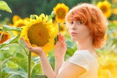 Ung flicka som tycker om naturen p? f?ltet av solrosor p? solnedg?ngen, st?ende av den h?rliga redheaded kvinnaflickan med solros arkivbilder