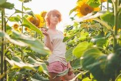 Ung flicka som tycker om naturen p? f?ltet av solrosor p? solnedg?ngen, st?ende av den h?rliga redheaded kvinnaflickan med solros royaltyfri fotografi