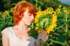 Ung flicka som tycker om naturen p? f?ltet av solrosor p? solnedg?ngen, st?ende av den h?rliga redheaded kvinnaflickan med solros arkivfoton