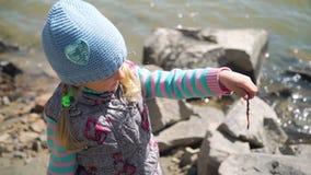 Ung flicka som undersöker en daggmask på fisketur