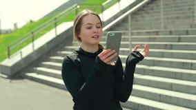 Ung flicka som utanför använder Smartphone lager videofilmer