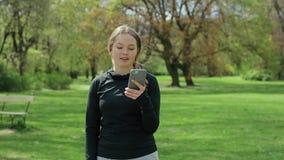 Ung flicka som utanför använder Smartphone på gröna träd lager videofilmer