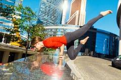 Ung flicka som utomhus gör yoga i stad Arkivbilder
