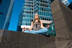 Ung flicka som utomhus gör yoga i stad Royaltyfri Bild