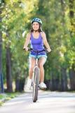 Ung flicka som utomhus rider en cykel Fotografering för Bildbyråer