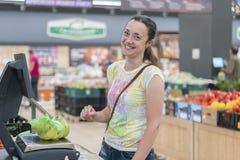 Ung flicka som väger bananen i supermarket shopping Kvinna som väger bio mat för bananfrukter i grönsaklager eller supermarket arkivbilder