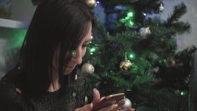 Ung flicka som väljer gåvor på smartphonen medan lögn på golvet bakgrundsjulen st?nger upp r?d tid arkivfilmer