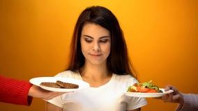 Ung flicka som väljer mellan kotletter och vegetarisk sallad, invecklat val royaltyfria bilder