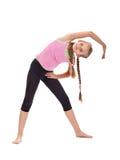 Ung flicka som värmer upp göra gymnastiska sträckning och böjlighet Fotografering för Bildbyråer