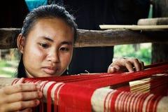 ung flicka som väver på en traditionell vävstol royaltyfria foton