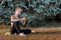 Ung flicka som vilar sammanträde på gräset Fotografering för Bildbyråer