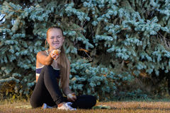 Ung flicka som vilar sammanträde på gräset Royaltyfria Bilder