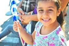 Ung flicka som vinkar en grekisk flagga Royaltyfri Foto