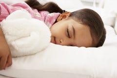 Ung flicka sovande i säng med den keliga leksaken Arkivbild