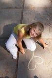 Ung flicka tecknar på den konkreta jordningen royaltyfri foto