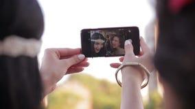 Ung flicka två fotograferar på smartphonen kvinnliga vänner som har gyckel, medan ta selfie Kvinnor som gör lyckliga framsidor oc arkivfilmer