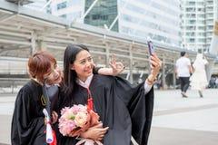 Ung flicka två tar ett foto med telefonen i beröm en graduati royaltyfri bild