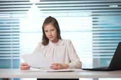 Ung flickaaffärskvinna i tillfällig kläder som nära sitter på en blick för tabell på dokument som arbetar på datoren royaltyfri foto