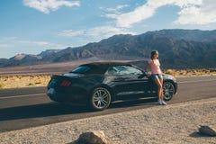 Ung flickaanseende av den svarta Ford Mustang GT Arkivbilder