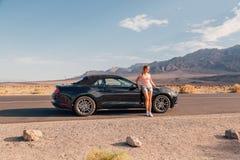 Ung flickaanseende av den svarta Ford Mustang GT Fotografering för Bildbyråer