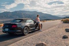 Ung flickaanseende av den svarta Ford Mustang GT Royaltyfri Foto