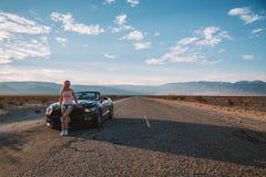 Ung flickaanseende av den svarta Ford Mustang GT Royaltyfri Bild