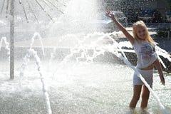 Ung flickaanseende i fontain Arkivbild