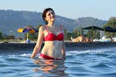 Ung flickaanseende i havsvatten på bakgrund av stranden Arkivbild